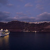 An evening sail off Santorini.  Lights of the town are coming on and the clouds are reflecting the setting sun.