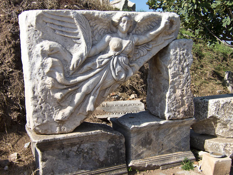 A carving of the goddess NIKE.  In Greek mythology, Nike was a goddess who personified victory, also known as the Winged Goddess of Victory. The Roman equivalent was Victoria.  Nike flew around battlefields rewarding the victors with glory and fame.