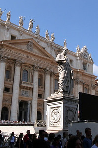 Facade of St. Peters (1612) and Statue of St. Peter (1847).  For perspective of the size of the facade, note that there are two groups of people seen here - one in the shade (probably behind this caption) in the foreground and the second at the base of those pillars.