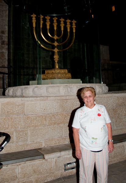 Sandy standing in front of a Menorah