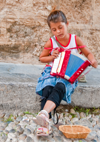 A local kid playing an accordion for Euros