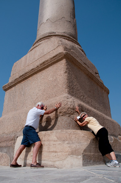 David and Judy pushing against the base of Pompey's Pillar