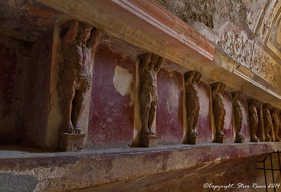 Close up detail of carvings along the wall of a bath house in Pompeii