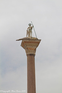 Sculpture of St. Mark slaying a dragon on top of a pillar in St. Mark's square, Venice, Italy.