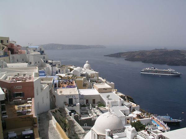 The town of Fira rises on the cliff above the ocean.
