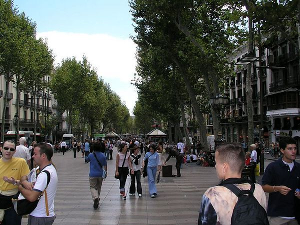 Las Ramblas is full of people. The sides of the street are jammed with tapas bars, restaurants, shops and 24 hour newspaper stands.<br /> Some of the restaurants have sidewalk dining in the center promenade complete with waiters.