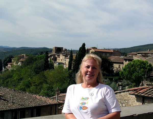 Sue standing near a wall on the edge of the town in San Gimignano