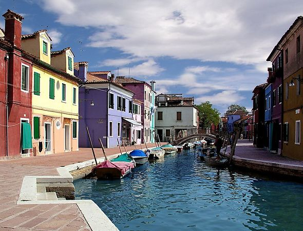 Colorful buildings along a canal in Burano, Italy with a boy fishing near a bridge.