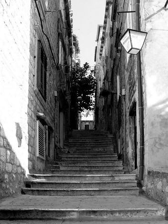 A narrow alley with steps leads to the next street.