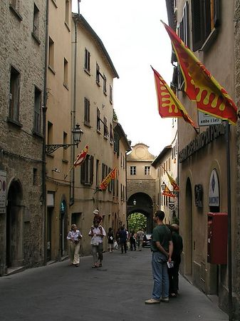 More flags decorate the narrow streets. Many of the doorways are arched.