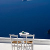 White chairs and table overlooking the mediteranian ocean on a clear day at Santorini, Greece with ship in the background.