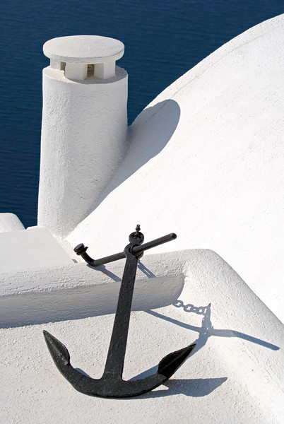 Boats anchor on white painted rooftop with sea in background taken at Santorini, Greece