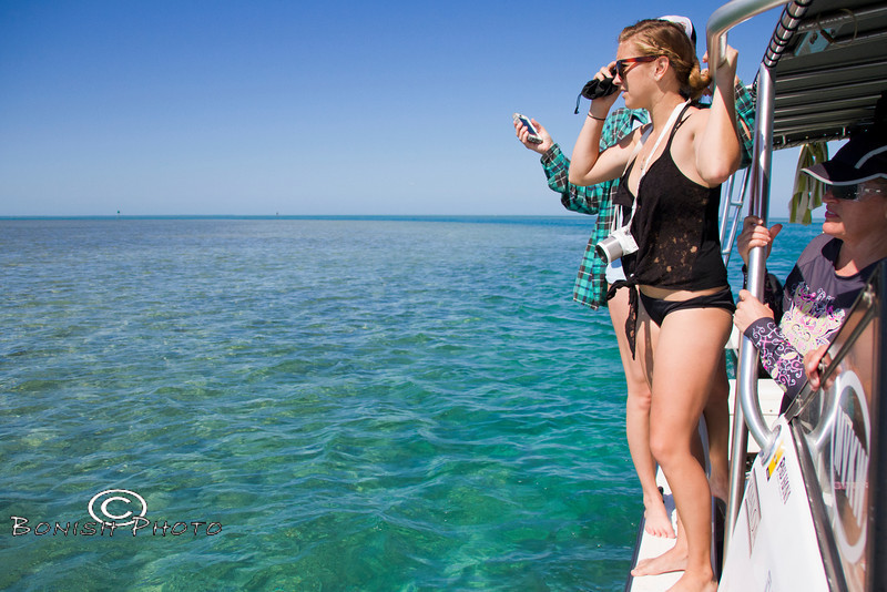 The girls are watching the sharks swim past the catamaran - Mellow Ventures Key West - Photo by Pat Bonish