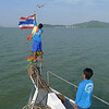 As the boat moves across the channel, we leave Thailand and enter the Myanmar waters. The crew change the flags, shown here taking down the Thai flag and ready to put up the Myanmar flag which rests on his shoulder.