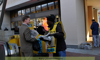 Washington Post's Express newspaper vendor busy chatting with a Metro rider.