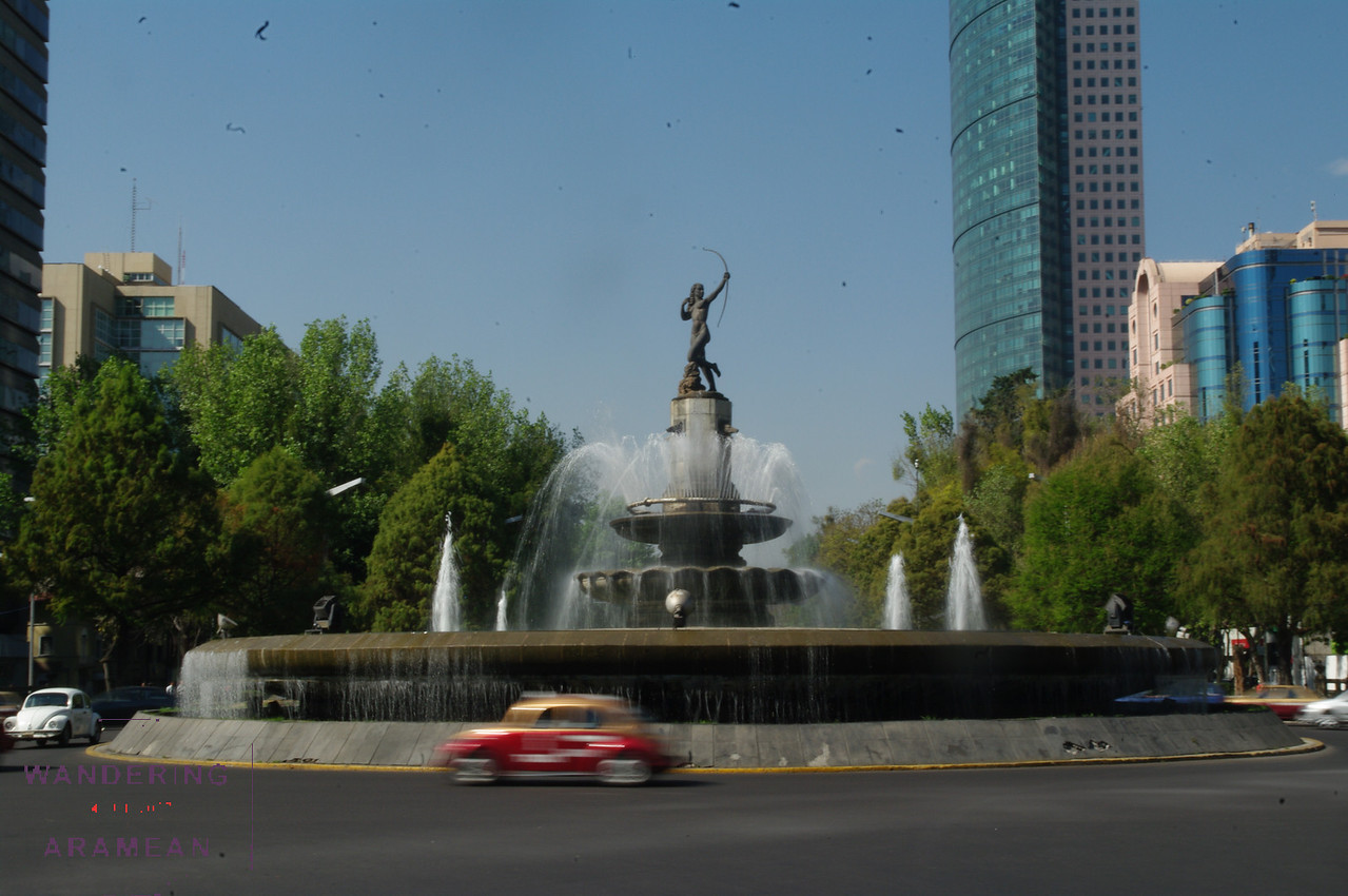 A fountain in the middle of one of the main avenues.