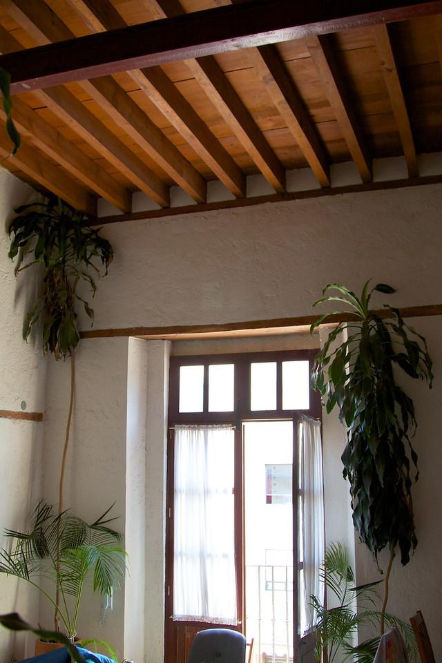 Wood-beamed ceiling, doors open to juliet balcony off of living room.