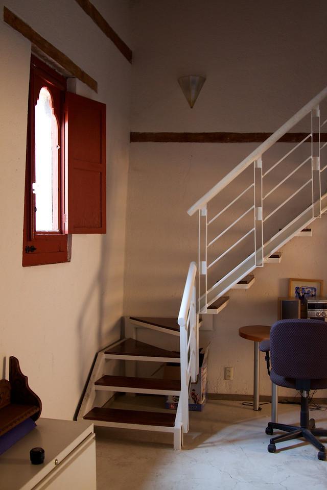 Stairs to lofted bedroom, cute window.