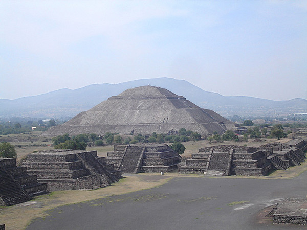 The Pyramid of the Sun.  A few people on its summit appear as little specks. It is speculated that it was intended to echo the shape ot the mountain seen behind it in this view from the Pyramid of the Moon.
