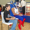This kid was going mano-a-mano with the luchadore next to him by playing him in a lucha libre video game. Note the video game controllers they're clutching.
