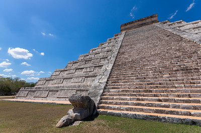 """El Castillo (Spanish pronunciation: [el kas'tiʎo], Spanish for """"the castle""""), also known as the Temple of Kukulcan (or sometimes Kukulkan), is a Mesoamerican step-pyramid that dominates the center of the Chichen Itza. Temple is dedicated to the feathered serpent god Quetzalcoatl, this is easily the most famous landmark of Chichén Itzá. The pyramid rises 24 meters above the plaza, plus an additional 6 meters for the temple on top. The base of the pyramid is 55.3 meters on each side. El Castillo represents the Snake Mountain, a mystic place in Maya folklore where creation first occurred. Snake Mountain is a design practice adopted in Teotihuican as well as the Aztec capital of Tenochtitlan. At Chichen Itza the design is brought to its full artistic maturity. The Maya were great mathematicians, inventing the concept of """"zero"""" long before western civilizations. They were also great astronomers, and El Castillo is the perfect marriage of these two sciences. The temple contains many references to the important Mayan calendar. Each of El Castillo's four sides has 91 steps which, when added together and including the temple platform, equals the 365 days of the solar year. Each of the nine terraces are divided in two, which makes 18, symbolizing the number of months in the Maya calendar. The terraces contain a total of 52 panels, referring to the 52-year cycle when both the solar and religious calendars converge. On the corners, the staircases have railings with carved feathered serpents, the open-jawed head at the foot and the rattle held high at the top. During the spring and autumn equinoxes, at the rising and setting of the sun, the corner of the pyramid casts a shadow in the shape of a snake, representing the god Quetzalcoatl. As the sun moves, the serpent slowly descends into the earth. During restoration of El Castillo in the late 1920s and early 1930s, archaeologists discovered it had been built upon an earlier temple. Researchers estimated that this construction dat"""