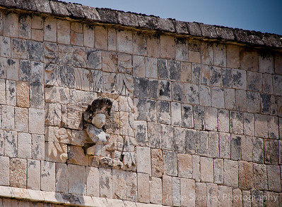Feathered serpent with a human head in its mouth on the side of the Temple of the Warriors, Chichen Itza