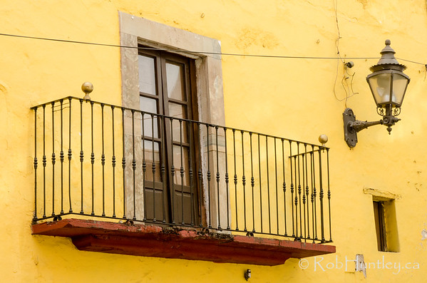 Lamp and Balcony on Yellow Stucco Wall