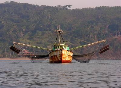 © Joseph Dougherty. All rights reserved.  Mexican fishing trawler at anchor in the bay, with booms down and nets out to dry.    Chacala, Nayarit Province, Mexico.