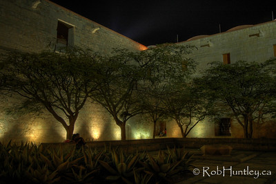 Church and former monastery of Santo Domingo, Oaxaca, Mexico. Night shot of the corner of the courtyard or square outside the church. © Rob Huntley