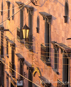Balconies and wires at sunset.