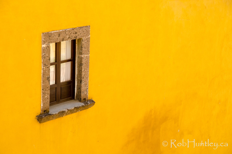 Window on a yellow wall.