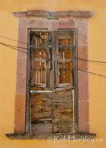Boarded-up window and wires.