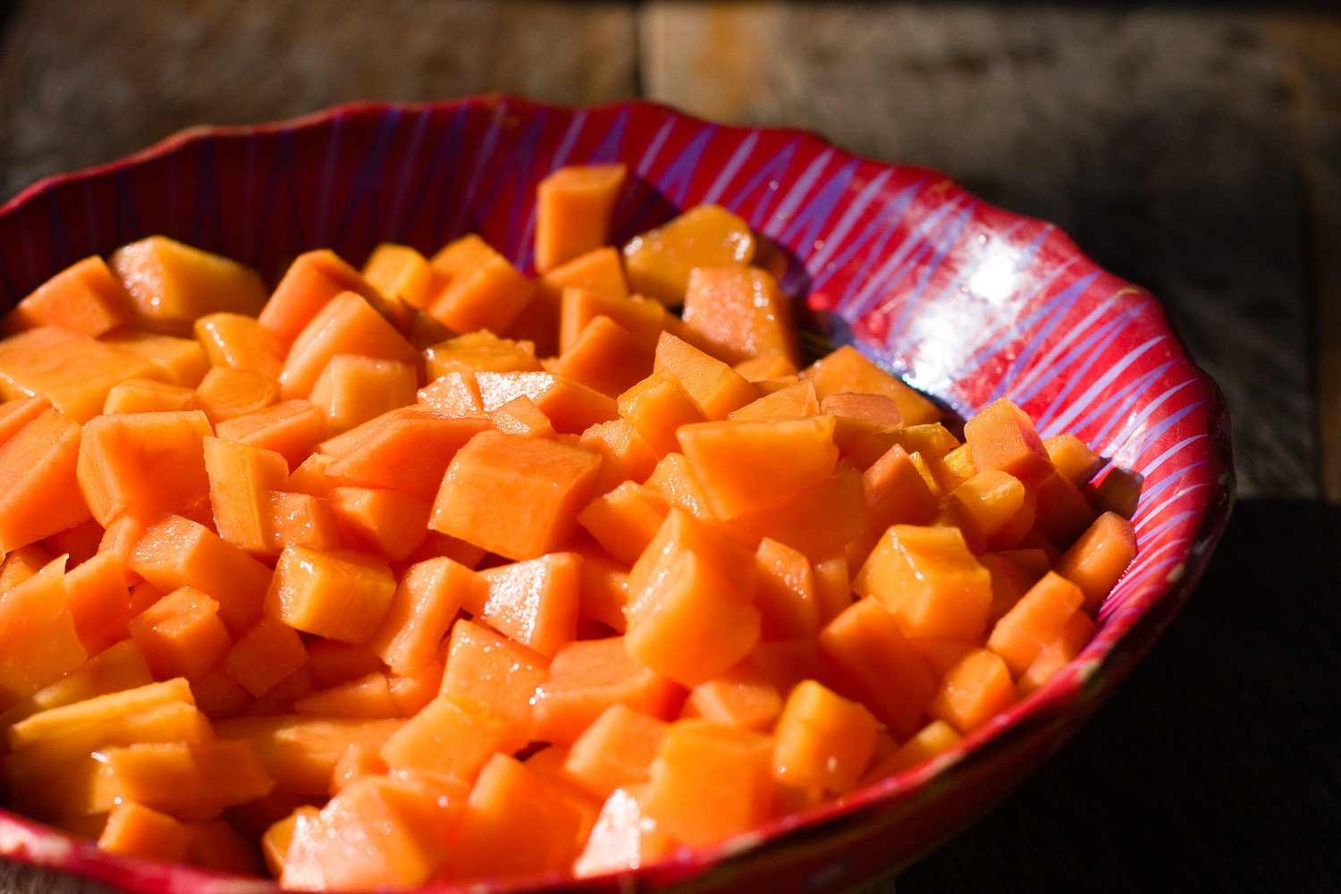 Papaya chunks in a red bowl in Cuba