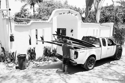 loading Abner's surfboard in front of his house