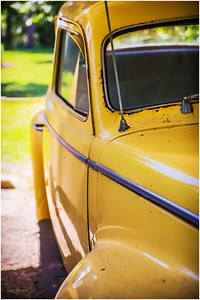 This canary yellow vintage car is parked in an old porch.