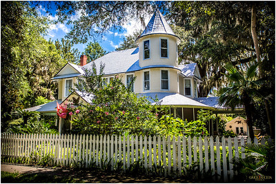 A home on main street with a little more northern look and feel adorned with Florida native plants and white picket fence.
