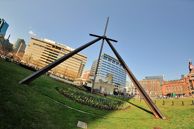 Under Sky / One Family, designed by Mark di Suvero, was commissioned by the City of Baltimore and dedicated along the Inner Harbor, east of the World Trade Center, on May 4, 1980. The site specific abstract Cor-Ten steel sculpture, measuring approximately 70 inches by 36 inches by 78 inches, consists of four large steel beams placed vertically, meeting, with a fifth beam resting horizontally. On the ground nearby is a large sculpture of a propeller blade resting in a bed of bark chips outlined by railroad ties.