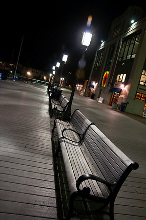 Empty benches line the boardwalk in front of the Torpedo Factory