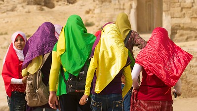 Local girls wearing colorful hijabs add some variety to the otherwise dull colors of the desert.