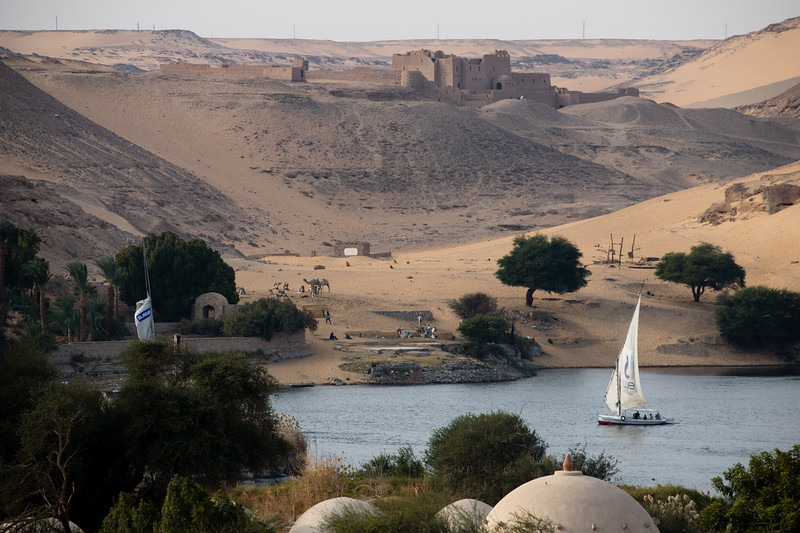 A felucca sails the Nile river near Aswan, with St Simeon Monastery in the background.