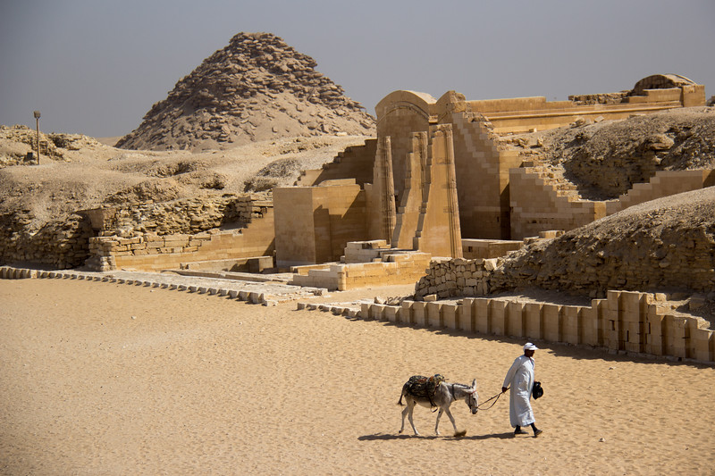 A local man leads a donkeuy past the entrance to the temple at Saqqara, Egypt.
