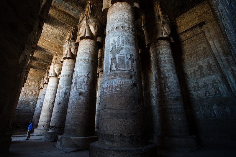 A tourist stands below ornately carved columns reach to the roof of Dendera Temple in Upper Egypt.