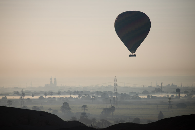 A hot air balloon rises in the early morning over Luxor, Egypt.