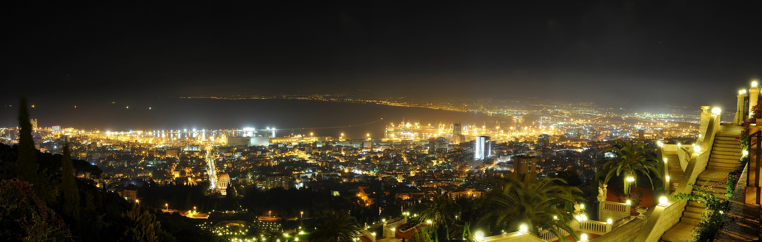 """Night lights of Haifa, Israel taken from Carmel looking down at the Bahá'í Shrine of the Báb (the round dome at left of the middle, and the steps in the near ground) and the Haifa port. Beyond is the Mediterranean Sea. This is a stitch of three photos. <a href=""""http://toplproject.wordpress.com/2008/10/28/a-couple-of-photos-from-haifa-israel/"""">Write up</a>."""