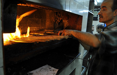 A kebab man cooks the food in a fired oven.