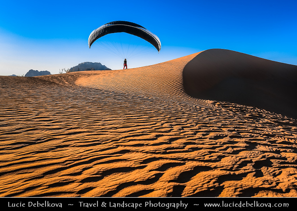 Jordan - Hashemite Arab Kingdom of Jordan - Wadi Rum - UNESCO World Heritage Site - The Valley of the Moon - Spectacularly scenic desert valley cut into the sandstone and granite rock in southern Jordan - Paragliding in stunning desert area with sand dunes at warm evening light