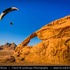 Jordan - Hashemite Arab Kingdom of Jordan - Wadi Rum - UNESCO World Heritage Site - The Valley of the Moon - Spectacularly scenic desert valley cut into the sandstone and granite rock in southern Jordan - Paragliding in stunning desert area over big natural arch carved by nature forces
