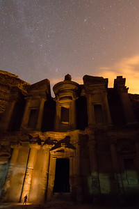 Petra's Monastery at Night, with a sky full of stars and the lights of Wadi Musa beyond.