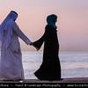 Middle East - GCC - Kuwait - Salmiya corniche - Arabian Gulf Street - Sea front with Kuwait City skyline and local Kuwaiti man in traditional arabic dress dishdasha holding hands with woman during Sunset