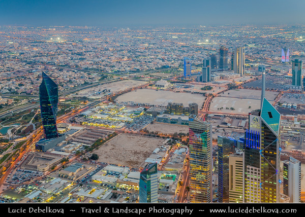 """Middle East - GCC - Kuwait - Kuwait City - View from Al Hamra Tower - Tallest skyscraper in Kuwait - City's Modern Skyline with highrise buildings including Al Tijaria Tower - Kuwait Trade Center inspired by a spiral or helix, body of the tower """"twists"""" by 80 degrees as it climbs to 218.2 m / 716 ft at Dusk - Twilight - Blue Hour - Night"""